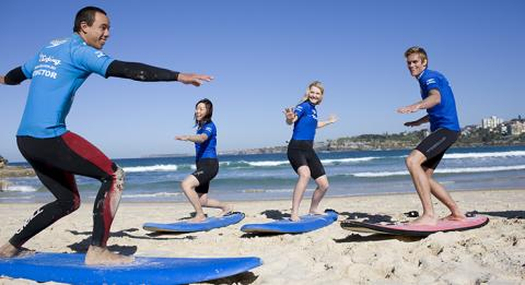 T​wo young women and a young man learning to surf with a 'Let's Go Surfing' instructor at Bondi Beach