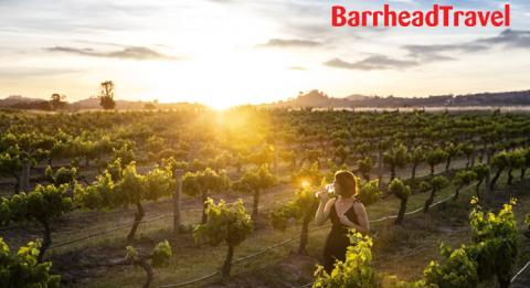 Woman enjoying a glass of wine and the sun set from the scenic grounds of Burnbrae Wines, Mudgee